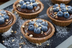 chocolate mousse with fresh blueberries and nuts in tartlets, horizontal, close-up