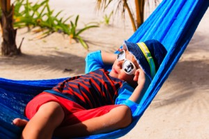 happy little boy relaxed in hammock on beach, family vacation